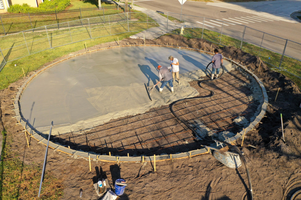 Crew pours the concrete base of a FitLot Outdoor Fitness Park